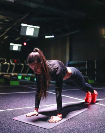 concentrated-sportswoman-doing-plank-exercise-at-gym-3875399