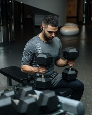 man-sitting-on-flat-bench-while-holding-two-dumbbells-3490348